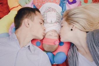 Padres jóvenes besando a su bebé