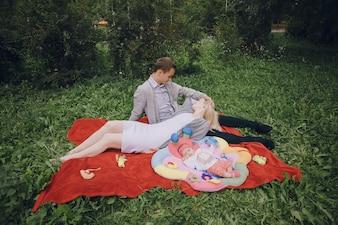 Padres jóvenes con su bebé sentados en la hierba