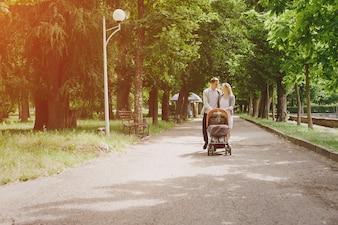 Padres paseando a su bebé en un cochecito