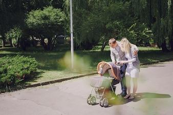 Padres sonriendo a su bebé en el cochecito