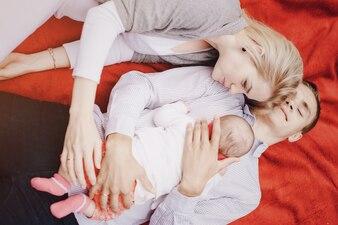 Padres tumbados con su bebé