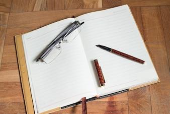 Páginas en blanco de una agenda con una pluma y un par de gafas