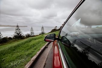Paisaje marino y la reflexión en una ventana de coche.