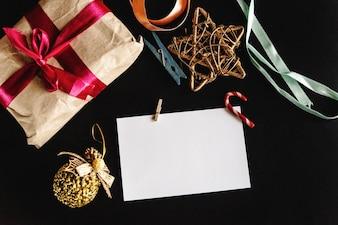 Paquete de regalo, adornos de navidad y un papel blanco