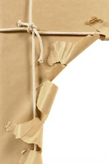 Paquete desgarrado envuelto en papel marrón abierto