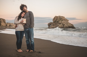 Pareja abrazada en la orilla de la playa sujetando una vela