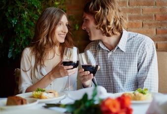 Pareja alegre brindando con copas de vino