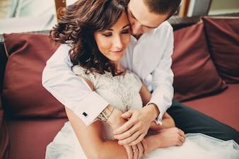 Pareja amorosa abrazándose en un sofá