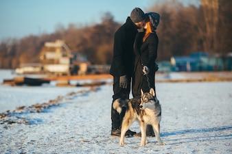 Pareja besándose mientras pasean a un perro
