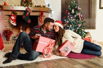 Pareja con cajas de regalos de navidad en su sala de estar
