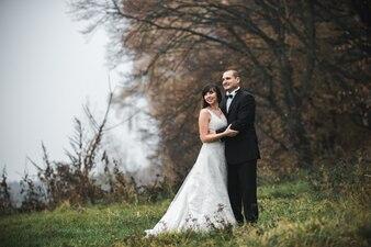 Pareja de la boda de pie en el campo