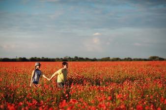Pareja de la mano en un campo de flores rojas