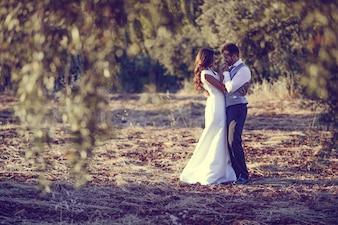 Pareja de novios abrazándose en el campo