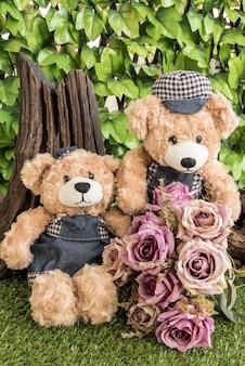 Pareja de osos de peluche con rosas en el jardín