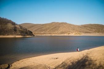 Pareja descansando junto al lago