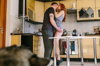 Pareja enamorada besándose en la cocina
