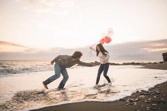 Pareja enamorada jugando y ella con globos en la mano