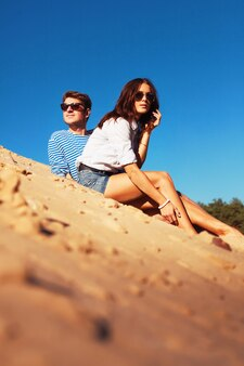 Pareja feliz con gafas de sol y sentados en la arena