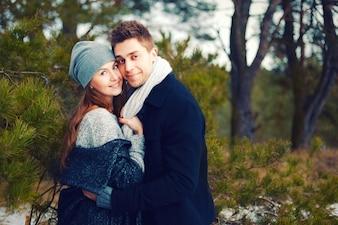 Pareja feliz con gorro y bufanda abrazándose al aire libre en invierno