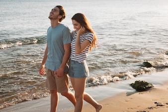 Pareja joven cogiéndose las manos en la playa