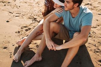 Pareja joven romántica sentada en la arena