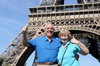 Pareja jubilada delante de la torre eiffel en parís