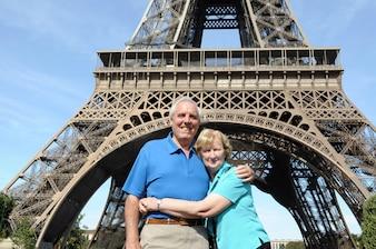 Pareja mayor abrazandose en frente de la torre eiffel en parís