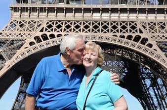 Pareja mayor besándose delante de la torre eiffel en parís