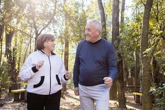 Pareja mayor hablando y riendo juntos en el parque