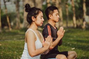 Pareja meditando con manos para rezar