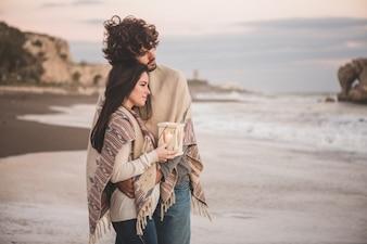 Pareja mirando el mar mientras sujetan una vela