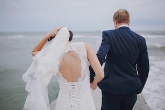 Pareja paseando y novia aguantandose el velo