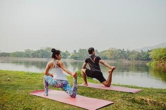 Pareja practicando yoga junto al lago
