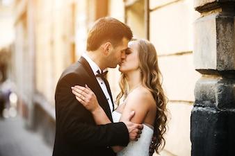 Pareja recién casada besándose en la calle