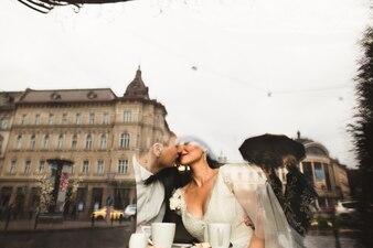 Pareja recien casada besándose reflejada en un cristal