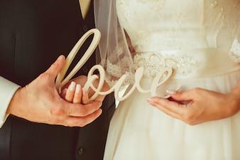Pareja recien casada sujetando las letras de  love