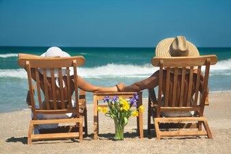 Pareja relajada en la playa con las manos unidas