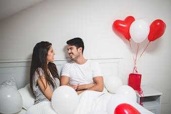 Pareja riendo tumbada en la cama con globos a su alrededor