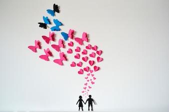 Pareja romántica de papel con corazones y mariposas volando