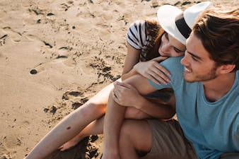 Pareja romántica joven sentada a lado del mar