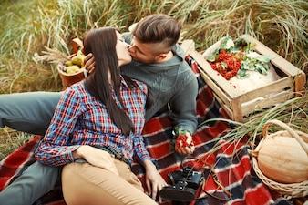 Pareja romántica sentada en el césped y besándose