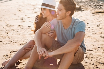 Pareja romántica sentada en la arena