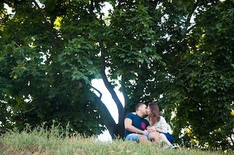 Pareja sentada besándose en el parque