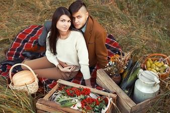 Pareja sentada en el césped con cajas de verduras