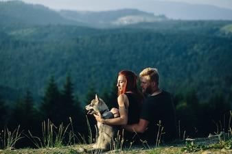 Pareja sentada en un campo verde mirando la naturaleza con su perro