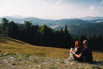 Pareja sentada en un campo verde mirando la naturaleza