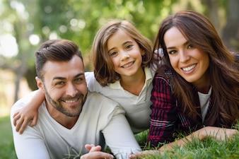 Pareja sonriendo tumbada en el césped con su hija