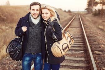 Pareja sonriente abrazándose en las vías del tren
