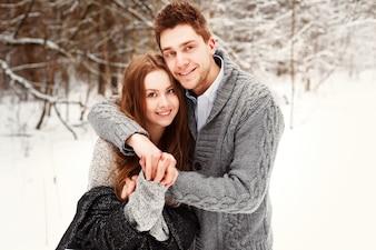 Pareja sonriente divirtiéndose juntos en invierno