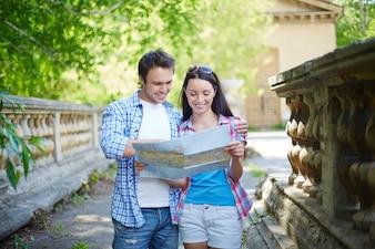 Pareja sonriente mirando un mapa de la ciudad